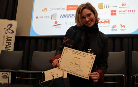 Image: Tessa, smiling, holds certificate which reads 'First Prize'