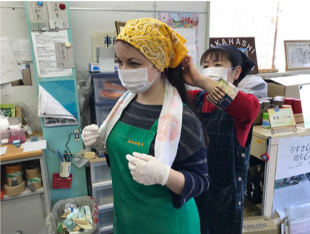 Mary, wearing a face mask and green apron has a yellow headscarf tied for her by a Takahashi Tea colleague. They are stood in the Takahashi Tea office
