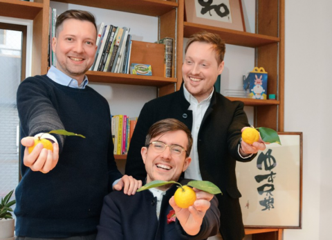 Three founders of Yuzu Kyodai smile to camera and hold yuzu fruits